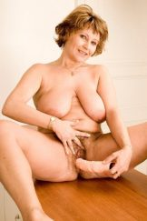 Hairy & busty mature Katka poses in her kitchen.